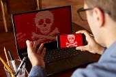 Man sits near laptop with phone blocked and encrypted by ransomware spyware asking for money. Laptop and smartphone infected by virus. Scary red skull crossbones on screen. Cyber security theme. poster