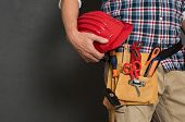 Closeup of hardhat held by construction worker on grey background. Bricklayer holding red helmet and kit tool. Closeup of craftsman hand holding tool belt with equipment on grey wall with copy space. poster