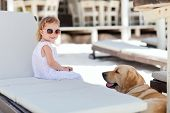 Little girl and golden retriever dog outdoors at beach poster