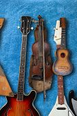 Musical instrument - Vintage bass guitar, acoustic, violin, balalaika on a blue plush background. poster