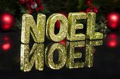 In capital letter written noel glitter effect over black poster