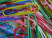A photograph of plastic coated paper clips. poster