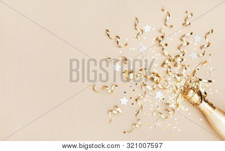 Champagne Bottle With Confetti Stars And Party Streamers On Gold Festive Background. Christmas, Birt