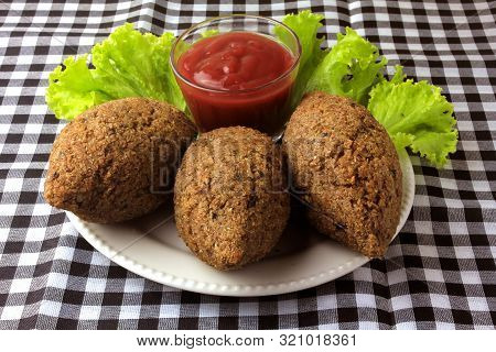 Kibbeh Fried With Tomato Sauce On A Plate, On Table Lined With Checkered Tablecloth