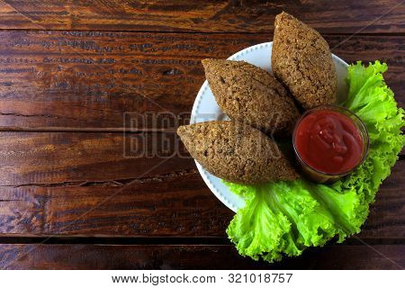 Fried Kibbeh With Tomato Sauce On A Plate, Over Rustic Wooden Table