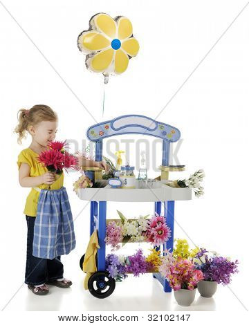 An adorable preschooler scrunching her nose behind the flowers she holds by her flower stand.  Signs on the stand left blank for your text.  On a white background.