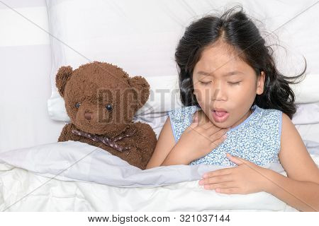 Little Girl Is Coughing And Sore Throat Lying On Bed With Toy Bear, Health Care Concept