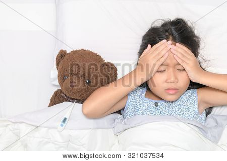 Sick Child. Asian Little Girl Headache And  Lying With Her Bear On Bed, Health Care Concept