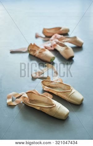 Old Faceless Pointe Shoes On The Floor. Female Ballet Footwear On Grey Background. Clothing Items Fo