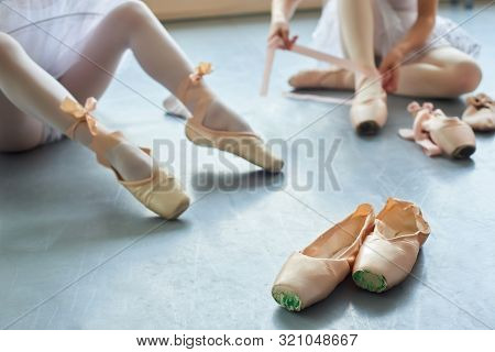 Pink Pointe Shoes For Ballerinas. Pair Of Ballet Slippers On Floor. School Of Traditional Ballet Dan