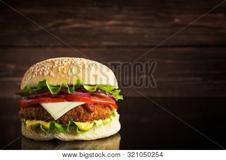 Delicious Fast Food. Delicious Tasty Burger With Lettuce, Cheese, Onion And Tomato On A Rustic Woode