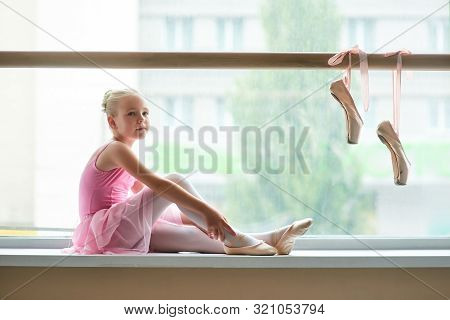 Beautiful Ballerina Posing On Window-sill. Portrait Of Young Ballet Dancer In Pink Dress And Pointe