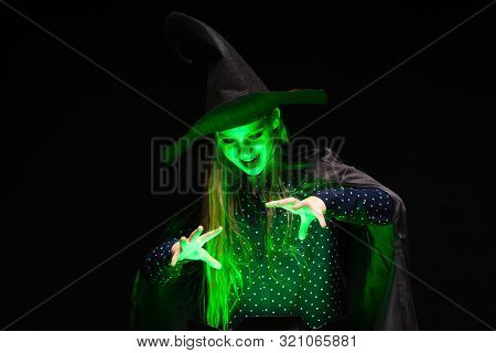 Halloween Witch Over A Pot Of Green Glowing Liquid Conjures Hands On Black Background. Beautiful You