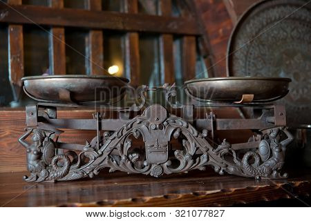 Cast Iron And Brass, Made In Azerbaijan. Vintage Weighing Scale On A Wooden Table .antique Measuring