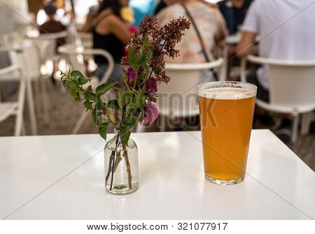 Focus On A Cold Glass Of Ipa Beer With Decorative Flowers On White Table In Lisbon Bistro