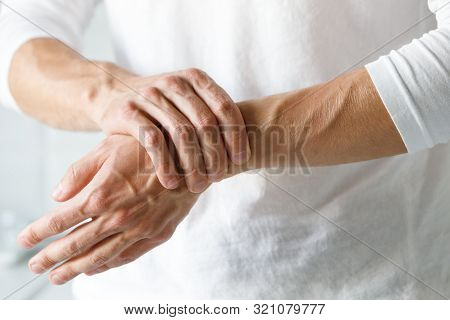 poster of Closeup of male arms holding her painful wrist caused by prolonged work on the computer, laptop. Carpal tunnel syndrome, arthritis, neurological disease concept. Numbness of the hand