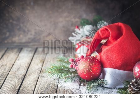 Christmas Background With Christmas Balls, Gift, Santa Hat And Snow On A Wooden Background