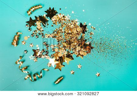 Golden Sparkles On Blue Background. Holiday Concept.