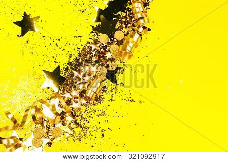 Golden Sparkles On Yellow Background. Holiday Concept.