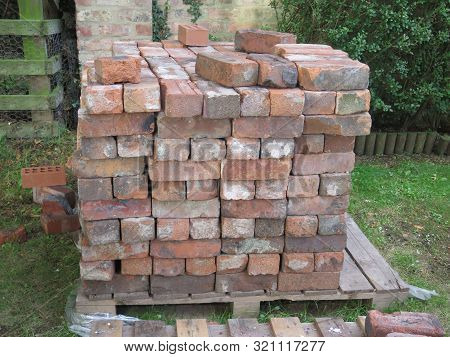 Old Rustic Bricks Piled On Pallet On Green Lawn