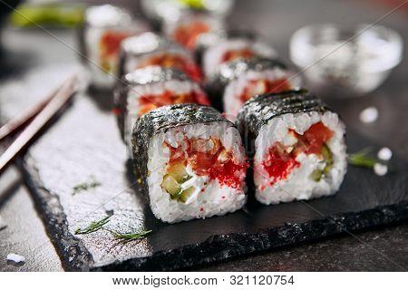 Macro photo of dragon roll with cream cheese, salmon, eel, rice, cucumber, flying fish caviar and nori. Dragon unagi maki rolls with raw red fish and tobiko on natural dark stone background close up