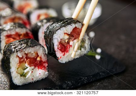 Chopstick holding dragon roll with cream cheese, salmon, eel, rice, cucumber, flying fish caviar and nori. Dragon unagi maki rolls with raw red fish and tobiko on natural dark stone background