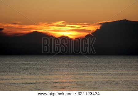 Bright sun sets in the clouds over the sea