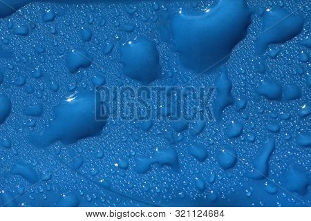 Drops of blue liquid on plastic surface