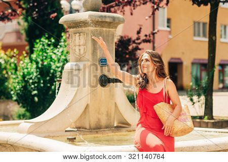 Summer Portrait Of Happy Woman With Beautiful Hair Style, Wearing Red Maxi Dress, Resting By The Fou