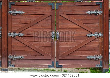 Close-up On A Brown Wooden Gate With Wrought Iron Hinged Patterns.