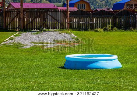 Blue Inflatable Rubber Pool On A Lawn Of Green Grass In The Courtyard Of A Country House With A Wood