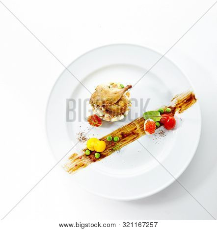 Olivier Salad or Russian Salad with Roasted Quail and Red Caviar on White Plate Isolated. Diced Potatoes, Carrots, Brined, Dill, Pickles, Green, Peas, Eggs, Onions, Mayonnaise and Spices Top View