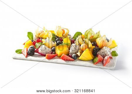 Exotic fruit plate with sliced mango, pitahaya, strawberries, blackberries, blueberries and cape gooseberries. Restaurant vegan fruits and berries platter, healthy meal isolated on white background