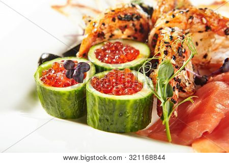 Fish platter with pink salmon, grilled eel, oil fish balyk and red caviar on elegant restaurant plate isolated on white background. Exquisite serving thin slices of salted and dried delicious seafood