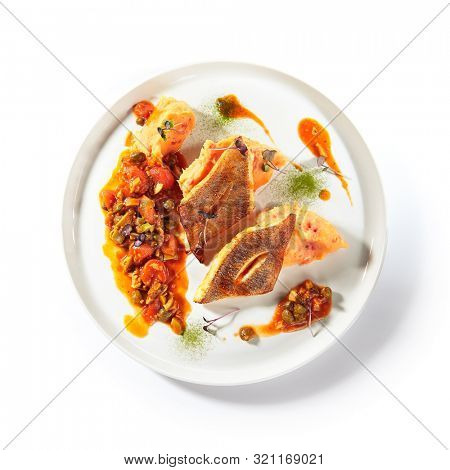 Pike perch or zander fillet with a side dish of tomatoes and capers served on a round platter. Restaurant main course with fried sander fish or barbecue pike meat on white plate isolated topview