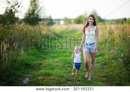 Young Mother Walks With Her Little Daughter Barefoot On A Country Road At Sunset. The Nanny Walks Wi