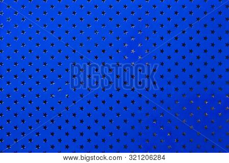 Navy Blue Background From Metal Foil Paper With A Pattern Of Sparkling Silver Stars, Closeup. Textur