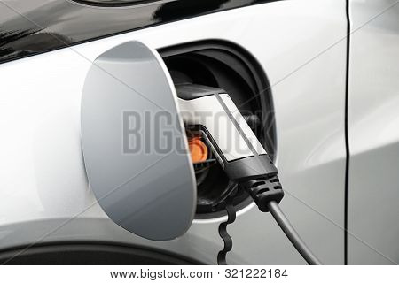 Ev Or Electric Car At Charging Station Plugged In With Power Supply Cable - E-mobility Or Green Ener