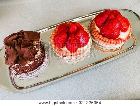 Irresistible strawberry and chocolate tarts served on a glass plate poster