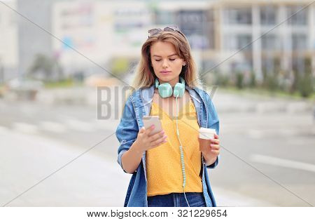 Woman Walking And Using A Smart Phone On A City Street - Millennial Girl Sending A Text Message Usin