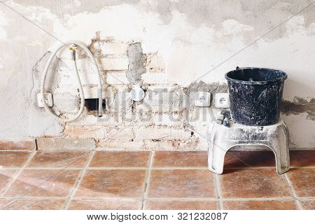 Black Dirty Bucket And Spatula Tools And White Brick Wall. Unfinished Room Reconstruction. Home Repa