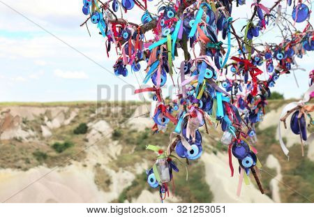 Many glass mascots - evil eye charms hang from a tree in Cappadocia, Pigeon valley, Anatolia, Turkey