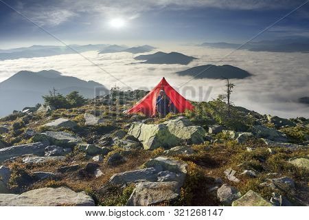 Athlete Drinks Coffee Tea With Ultralight Modern Equipment On Top Of An Alpine Mountain With Fog. A