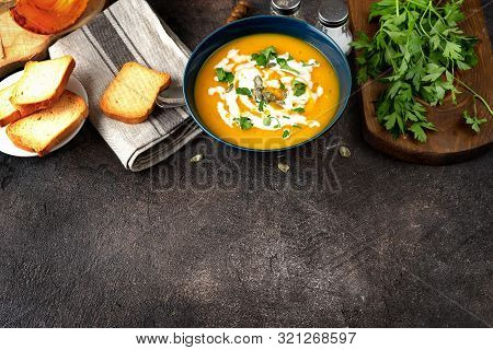 Top View Of Pumpkin Soup And Bread On Dark Vintage Wooden Background
