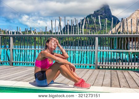 Fitness workout during vacation holiday travel. Asian fit woman tired sweating after endurance training at overwater bungalow on luxury getaway.