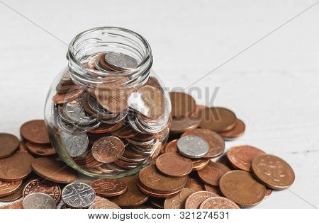 Full Jar Of Coins On A Table, Surrounded By Loose Change. Money Savings Concept With Copy Space.