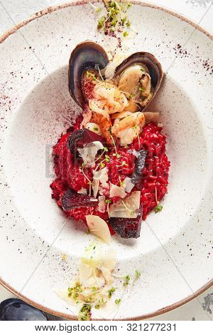 Top view of red beetroot risotto with chrimps, prowns, mussels and parmesan cheese. Exquisite serving beet seafood paella with shells, greens and spices topview