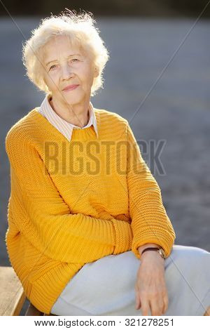 Outdoors Portrait Of Beautiful Smiling Senior Woman With Curly White Hair. Elderly Lady Walking In A