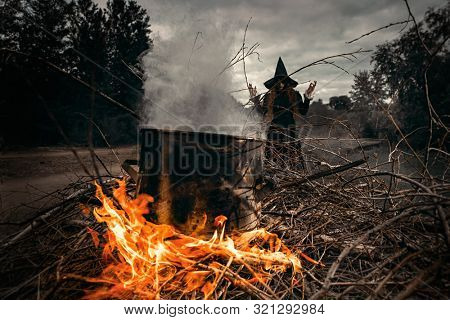 A portrait of an angry witch near the fire cooking spell. Magic, dark force, spell.
