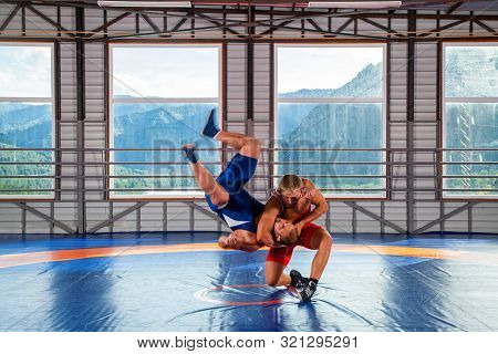 Greco-Roman wrestling training, grappling. Two greco-roman  wrestlers in red and blue uniform making a thigh throw  on a wrestling carpet in the gym.The concept of male wrestling and resistance poster